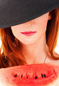 Beautiful woman with watermelon and black hat — Stock Photo