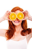 Junge fröhliche frau mit orangen in ihren händen — Stockfoto