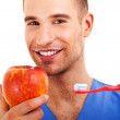 A young man brushing his teeth and holding apple isolated on whi — Stock Photo #28315435