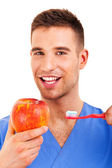 A young man brushing his teeth and holding apple isolated on whi — Stock Photo