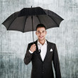 Man by the wall with umbrella in his hand — Stock Photo