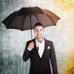 Businessman in rain and sun holding umbrella — Stock Photo #28887539
