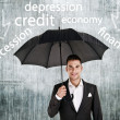 Stock Photo: Businessman holding an umbrella protect from problems