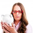 Upset woman wearing glasses holding piggy bank. Expensive eyewea — Stock Photo