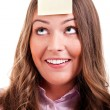 Young woma with yellow sticky note on forehead — Stock Photo #29166791