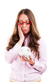 Upset woman wearing glasses holding piggy bank. Expensive eyewea — Stok fotoğraf