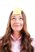 Young woma with yellow sticky note on forehead — Stockfoto