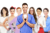 Young doctor holding piggy bank — Stock Photo