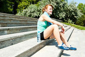 Sport and lifestyle concept - woman resting after doing sports o — Stock Photo