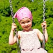 Adorable little girl having fun on a swing — Stock Photo