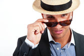 Fashion young man holding his fashionable sunglasses — Stock Photo