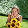 Young woman with a bouquet of sunflowers in the field closed eye — Stock Photo