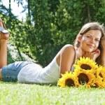 Beautiful woman enjoying daisy field, nice female lying down in — Stock Photo
