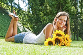 Beautiful woman enjoying daisy field, nice female lying down in — ストック写真
