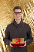 Happy young man carries present over gold background — Stock Photo