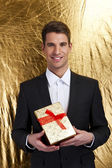 Happy young man carries present, over gold background — Stock Photo