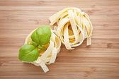 Italian pasta fettuccine nest on cutting board — Stock Photo