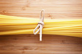Bundle of Italian spaghetti pasta tied with string lying on old — Stock fotografie