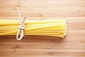 Bundle of Italian spaghetti pasta tied with string lying on old — Stockfoto