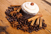 Chocolate cupcake, coffee beans, cinnamon, star anise on sacking — Stock Photo