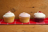 Photo of 3 cupcakes on wooden background — Stock Photo