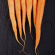 Raw fresh carrots with tails, top view — Stock Photo