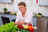 Jovem na cozinha preparando salada — Foto Stock
