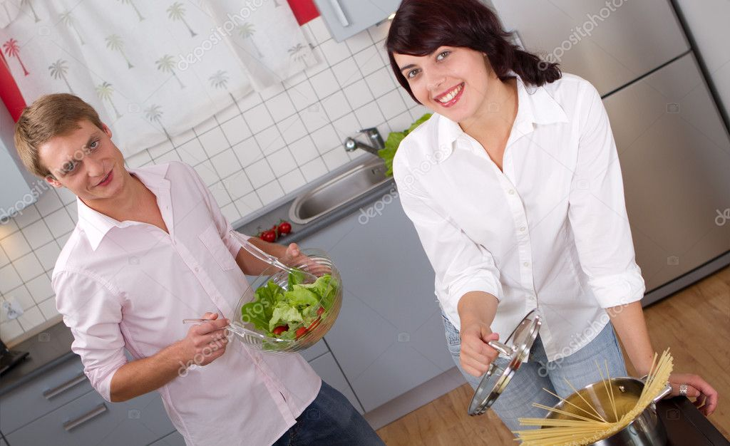 Happy young couple in the kitchen preparing dinner — Стоковая фотография #16287037
