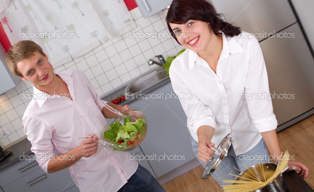 Happy young couple in the kitchen preparing dinner — Foto Stock #16287037