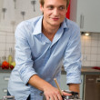 Handsome man cooking in the kitchen — Stock Photo