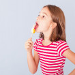 Stock Photo: Little girl licking lollipop