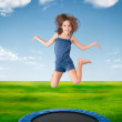 Cheerful girl jumping on a meadow — Stock fotografie