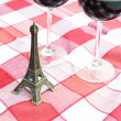 Little Eiffel tower and pair of wineglasses on table — Stock Photo #20760105