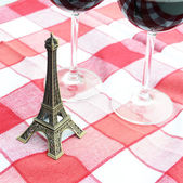 Little Eiffel tower and a pair of wineglasses on the table — Stock Photo