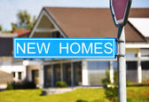NEW HOMES sign against house — Stock Photo