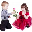 Stock Photo: The little boy gives a rose to a girl in a red dress