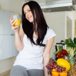 Woman drinking fresh orange juice in kitchen — Stock Photo #27577851