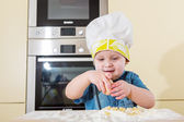 Child baking cupcakes in kitchen at home — Stock Photo