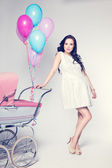 Sexy woman with baby stroller — Stock Photo