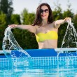 Woman in the garden splashing water from pool — Stock Photo #45959013