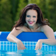 Woman in the garden splashing water from pool — Stock Photo #45959061