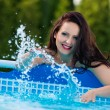 Woman in the garden splashing water from pool — Stock Photo #45959119