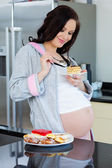 Beautiful pregnant woman eating a cake — Stock Photo