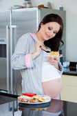 Beautiful pregnant woman eating cake — Stock Photo