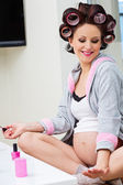 Pregnant woman with hair rollers getting nail treatment — 图库照片