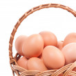 Eggs with eggshell in wickerwork basket — Stock Photo