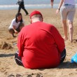 Fat man on the beach - Stock Photo