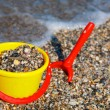 Plastic spade and bucket in sand — Stock Photo #14408001
