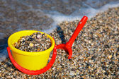Plastic spade and bucket in sand — Stock Photo