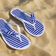 Flip-flops on sand beach — Stock Photo